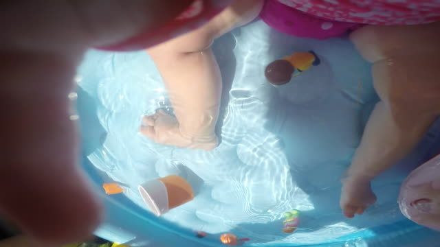 vidéos et rushes de a baby girl playing inside of a plastic swimming pool on a sunny day. - pataugeoire