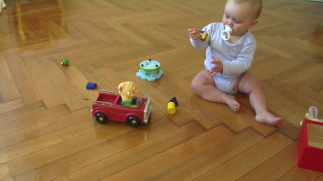 ws ha baby girl (6-11 months) playing on parquet floor, berlin, germany - 6 11 mesi video stock e b–roll