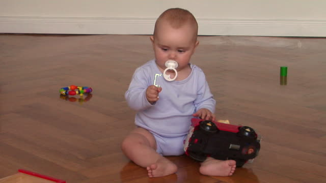 ws baby girl (6-11 months) playing on parquet floor, berlin, germany - 6 11 mesi video stock e b–roll