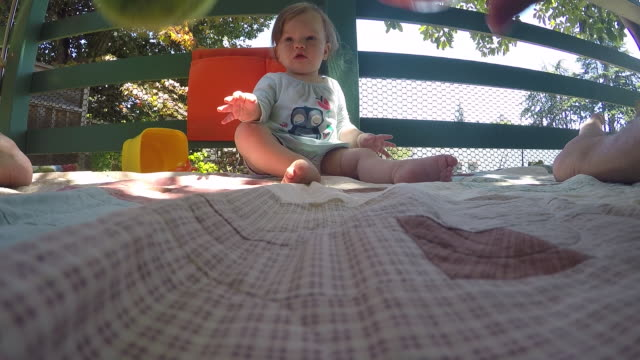 vidéos et rushes de a baby girl playing outdoors on the porch of a house. - jouet