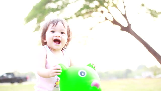 Baby girl playing rocking at horse at outside playground