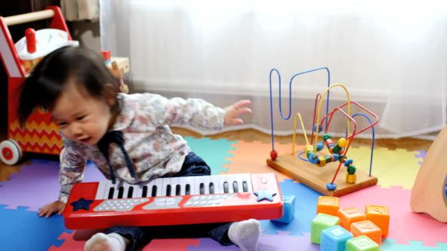 vídeos y material grabado en eventos de stock de niña jugando en la casa de juguete - piano