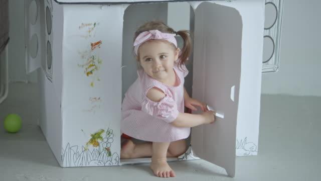 baby-mädchen spielen spielzeug haus, slow-motion - spielzeughaus stock-videos und b-roll-filmmaterial
