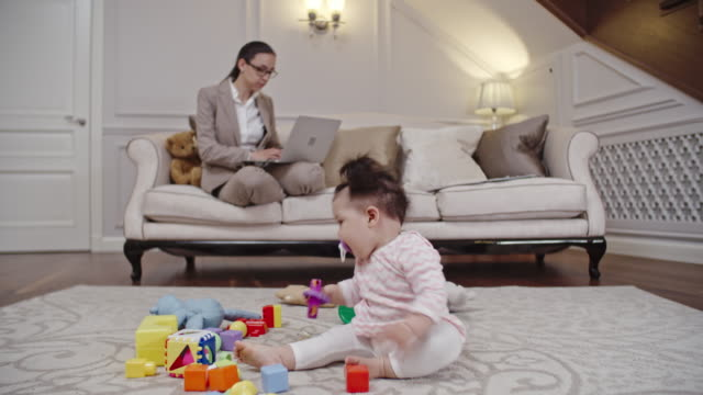 Baby girl playing while mother working from home