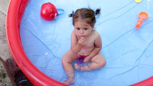 baby flicka leker med ett sugrör i poolen och ha kul - flickbaby bildbanksvideor och videomaterial från bakom kulisserna