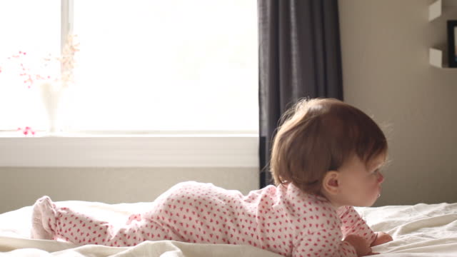 a baby girl playing with different toys and crawling on a bed indoors. - next to stock videos and b-roll footage