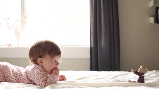 A baby girl playing with different toys and crawling on a bed indoors.