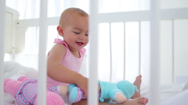 Baby girl playing with dolls