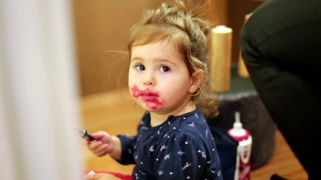 Baby girl playing with makeup and mimic her mom