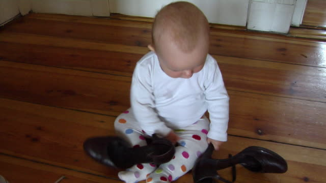 ms ha baby girl (6-11 months) playing with pair of shoes, berlin, germany - 6 11 månader bildbanksvideor och videomaterial från bakom kulisserna