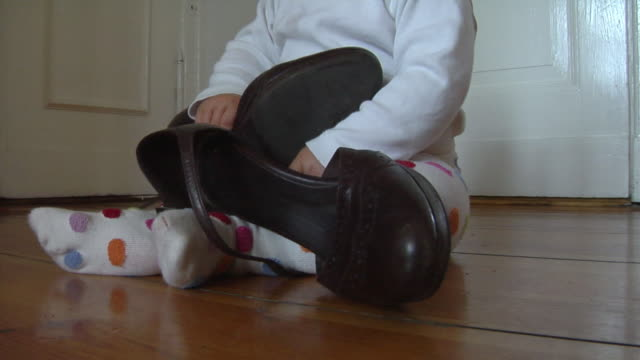 stockvideo's en b-roll-footage met cu baby girl (6-11 months) playing with pair of shoes, berlin, germany - stippen
