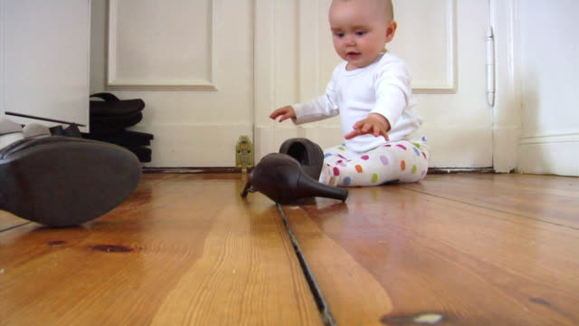 ws baby girl (6-11 months) playing with pair of shoes, berlin, germany - 6 11 månader bildbanksvideor och videomaterial från bakom kulisserna