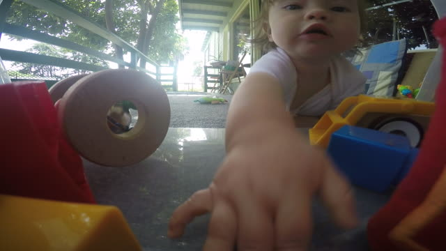 a baby girl playing with toys outside on a porch. - babies only stock videos & royalty-free footage