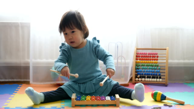 baby girl playing xylophone at home