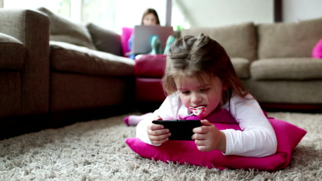 baby girl plays on phone - pacifier stock videos and b-roll footage