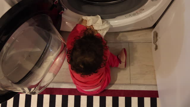 baby girl puts her clothes in the washing machine - utensil stock videos & royalty-free footage