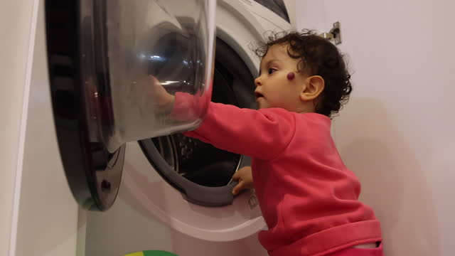 baby girl puts her clothes in the washing machine - innocence stock videos & royalty-free footage