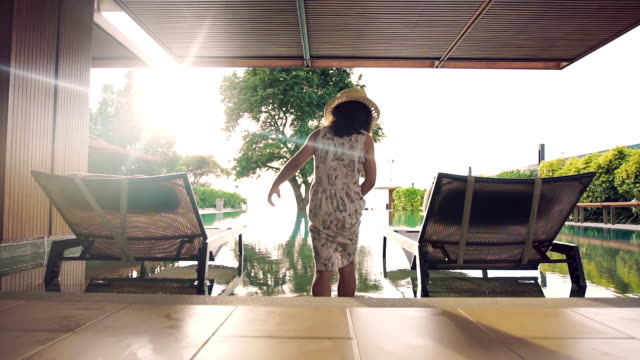 vídeos de stock, filmes e b-roll de menina na espreguiçadeira à beira da piscina de relaxamento - lago infinito
