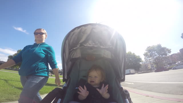 a baby girl riding in a stroller on a sunny day near a farmers market and lake. - sportkinderwagen stock-videos und b-roll-filmmaterial