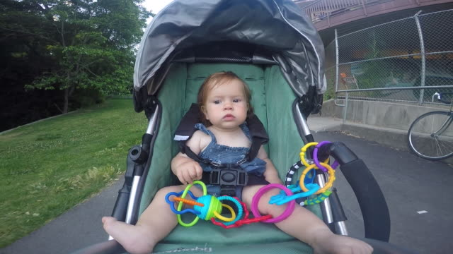 A baby girl riding in a stroller outside in a residential neighborhood.