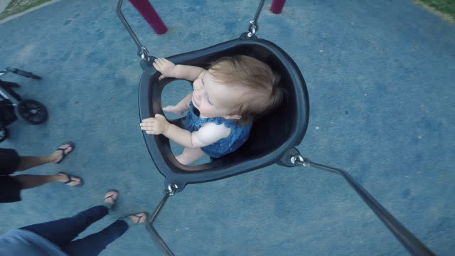 A baby girl riding in a swing outside at a park.