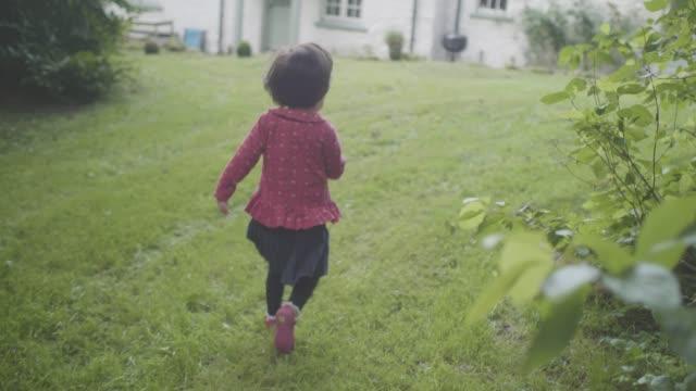 春の家の庭で走っている女の赤ちゃん - 夏休み点の映像素材/bロール