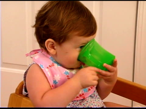 Baby girl sipping from cup