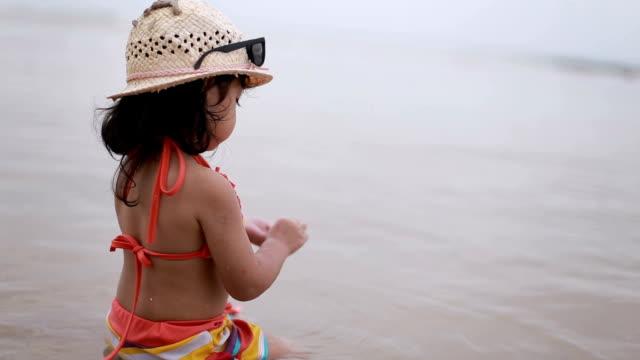 シェル遊んでビーチに立地の女の子を赤ちゃんし、楽しむ - 熱帯気候点の映像素材/bロール