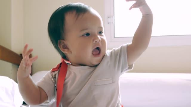 ベッドの上で座って遊んでいる女の赤ちゃん - 赤ちゃんのみ点の映像素材/bロール