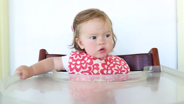 A baby girl sitting in a high chair eating strawberries and milk.