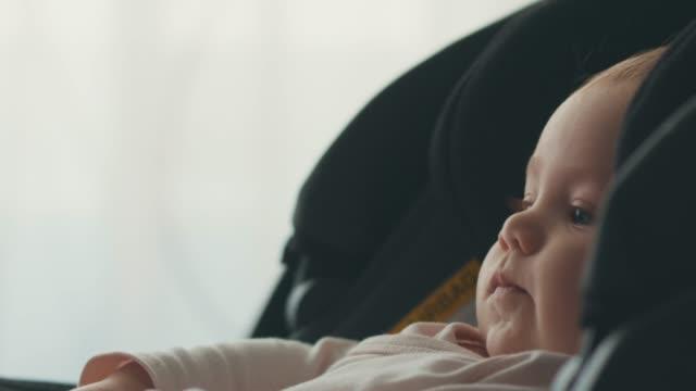 baby flicka sitter i bilstol - 6 11 månader bildbanksvideor och videomaterial från bakom kulisserna