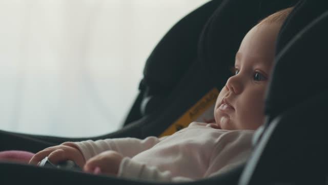 babymädchen sitzen im autositz - 6 11 monate stock-videos und b-roll-filmmaterial