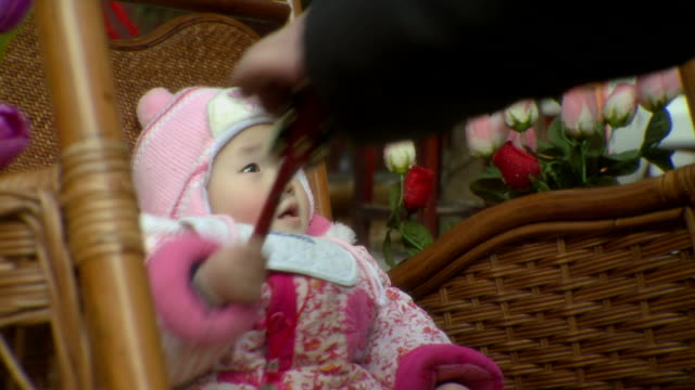 CU Baby girl sitting in hanging wicker chair outdoors and playing with toy rattle drum, Changsha, Hunan, China