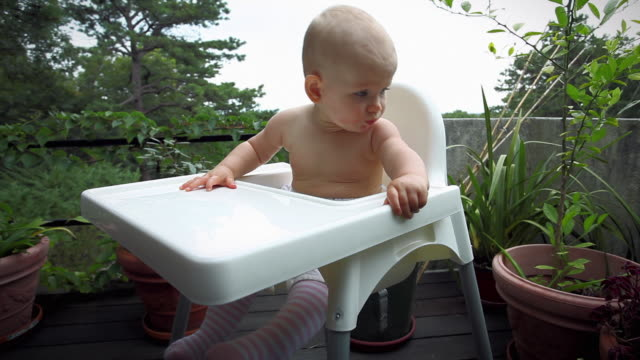 ms baby girl (6-11 months) sitting in high chair being fed by father in patio / water mill, new york, usa - 6 11 months stock videos & royalty-free footage
