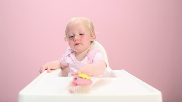 vídeos y material grabado en eventos de stock de baby girl sitting in highchair eating cupcake - sentado
