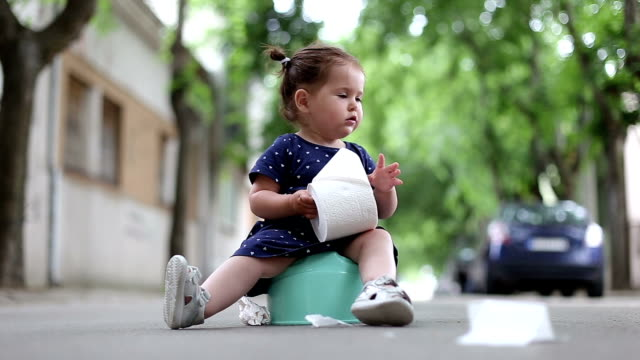 baby girl sitting on a potty outdoors and holding toilet paper - defecating stock videos and b-roll footage
