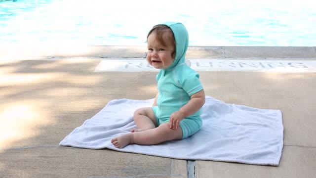 vídeos de stock, filmes e b-roll de a baby girl sitting on a towel next to a outdoor pool. - toalha de praia