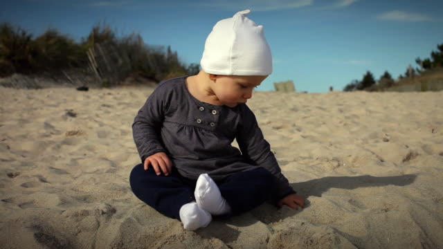 vídeos y material grabado en eventos de stock de ws baby girl (6-11 months) sitting on beach playing with sand / water mill, new york, usa - 6 11 meses