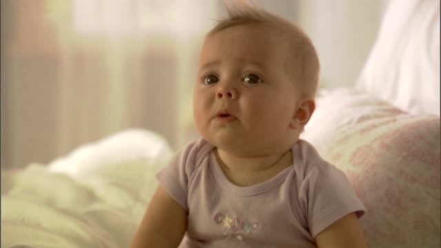 vídeos de stock e filmes b-roll de cu, baby girl (6-9 months) sitting on bed - 6 11 meses