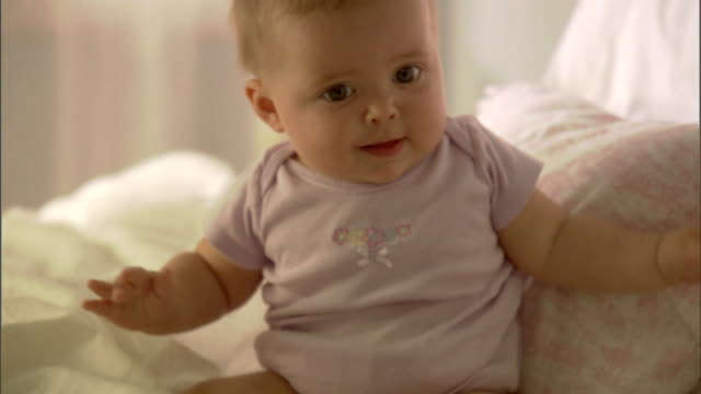 CU, Baby girl (6-9 months) sitting on bed