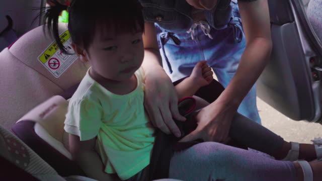 vídeos y material grabado en eventos de stock de niña sentada en el asiento con cerradura de madre para seguridad. - lanzacohetes