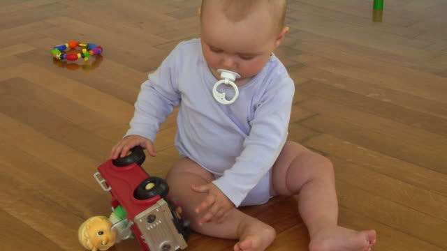 ms baby girl (6-11 months) sitting on floor playing with toy car, berlin, germany - 6 11 months stock videos & royalty-free footage