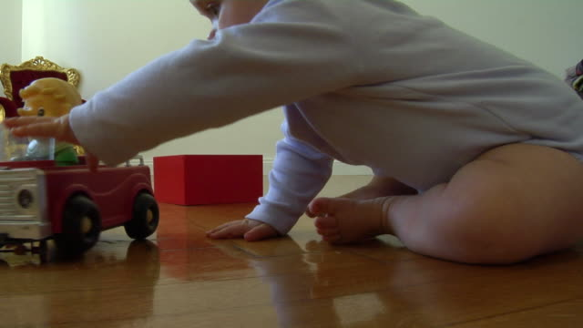 cu baby girl (6-11 months) sitting on floor playing with toy car, berlin, germany - babies only stock videos & royalty-free footage
