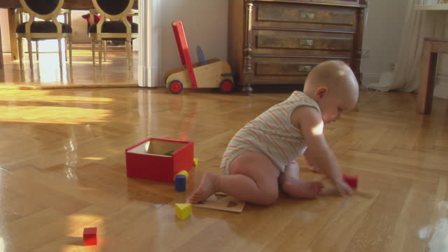 MS Baby girl (6-11 months) sitting on floor playing with wooden blocks, Berlin, Germany