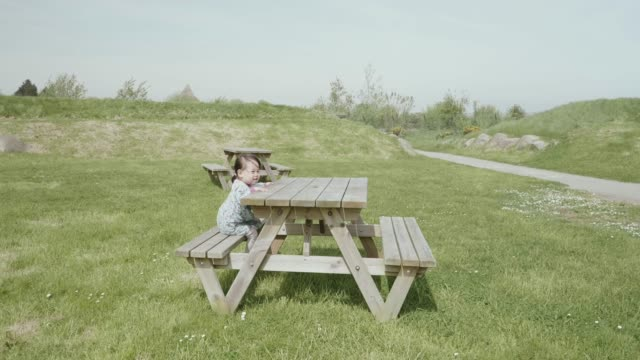 Baby girl sitting on picnic table