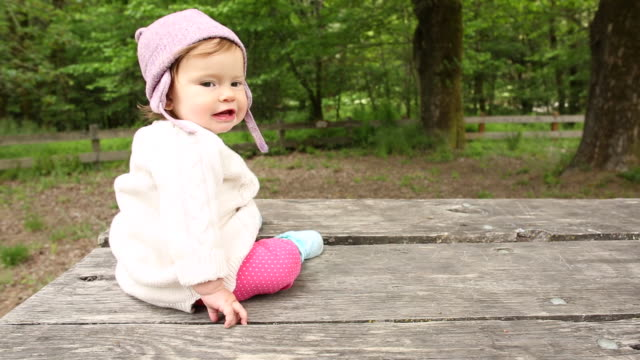 a baby girl sitting on top of a picnic table outdoors in a park with trees around her. - picnic table stock videos & royalty-free footage