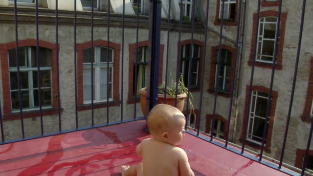 vidéos et rushes de ms tu td baby girl (6-11 months) sitting then crawling by wading pool on balcony, berlin, germany - 6 11 mois