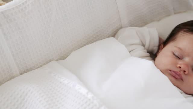 baby girl sleeping in bassinet - tutina video stock e b–roll