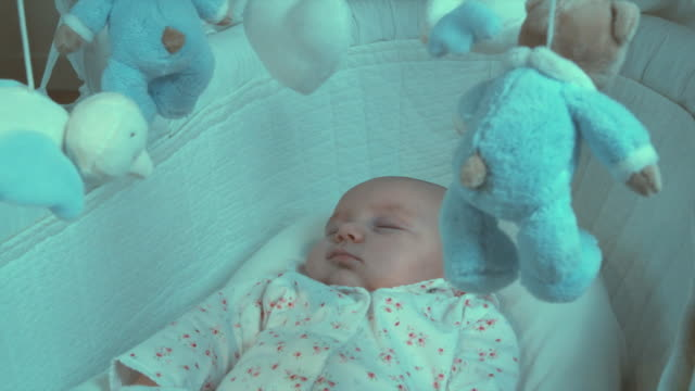 CU Baby girl (2-5 months) sleeping in Moses basket with toy mobile turning over her head, Brussels, Belgium