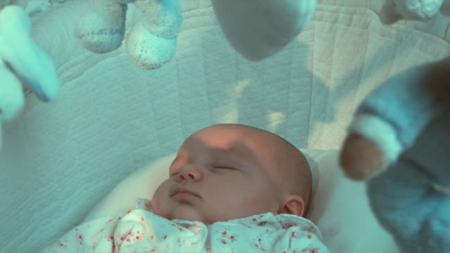 cu baby girl (2-5 months) sleeping in moses basket with toy mobile turning over her head, brussels, belgium - shadow stock videos & royalty-free footage